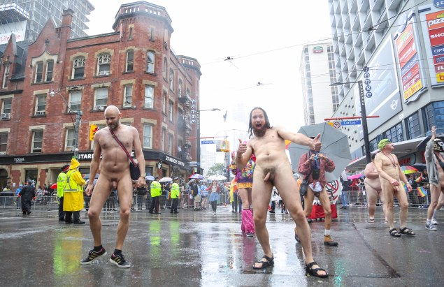 Jade Sambrook performing a side-glide à la Michael Jackson while walking naked with the TNTmen group along the route of the 2015 Toronto Pride Parade.