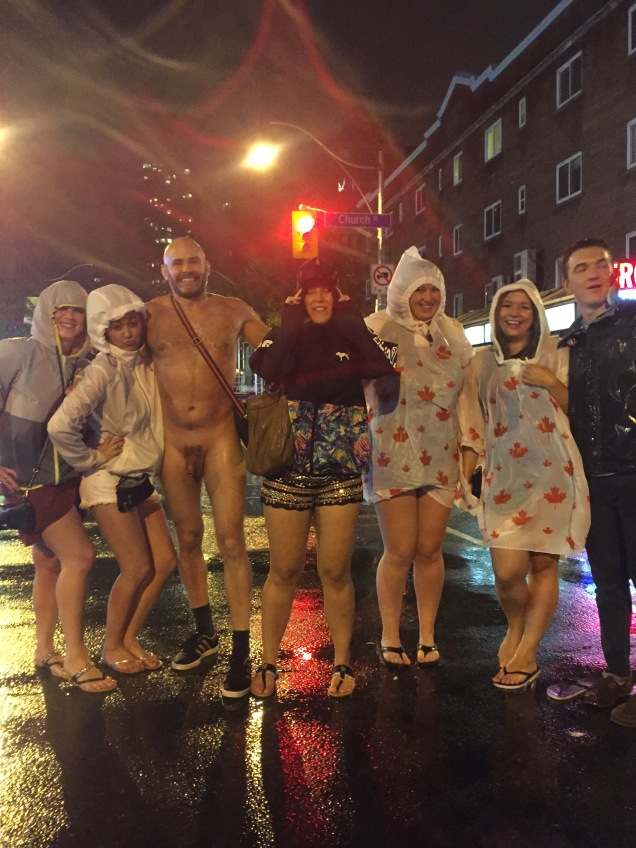 Jade Sambrook posing for a photo with people while naked in the rain on Church Street at Toronto Pride 2015.