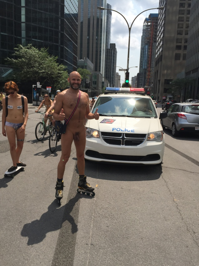 Jade Sambrook naked on rollerblades in front of a police car at the 2015 daytime edition of the World Naked Bike Ride in Montreal.