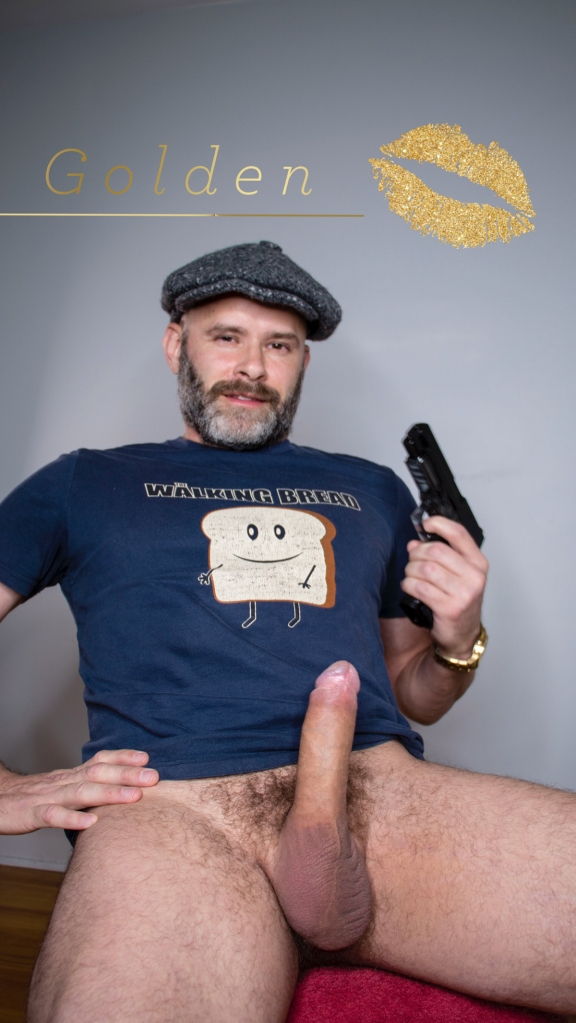 Playgirl style photo of Jade Sambrook posing nude (bottomless) while holding gun in one hand while his erect penis is displayed