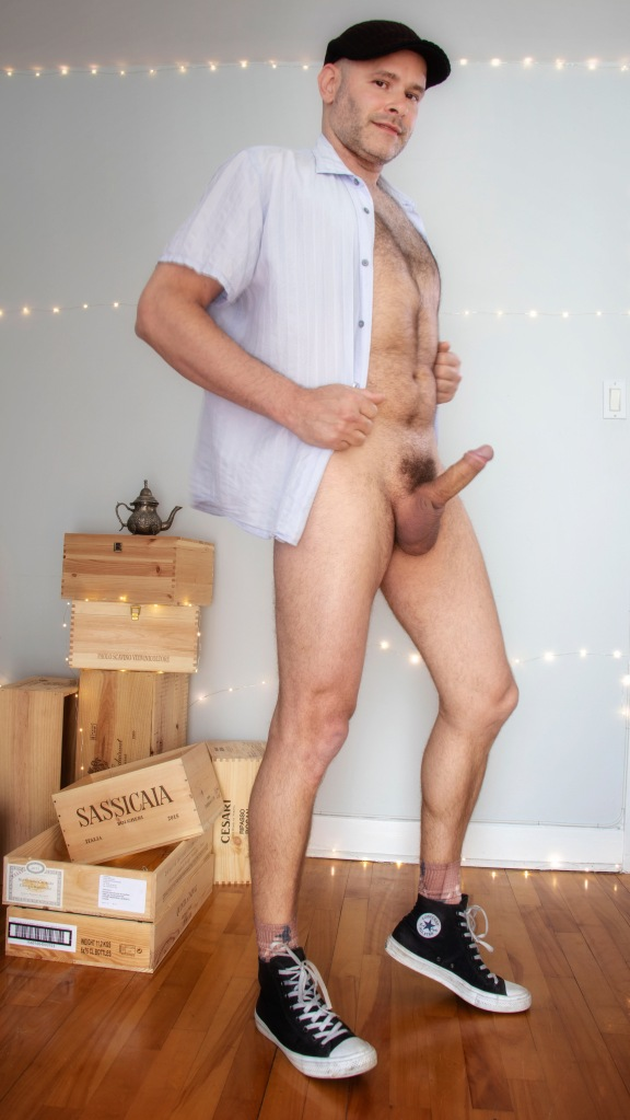 Jade Sambrook standing naked wearing only shoes and an open shirt with his erect penis visible