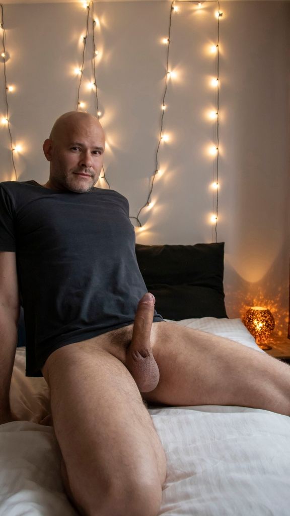 A window lit photo of a bottomless Jade Sambrook posing on a bed with his naked erect penis in full view